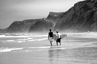surfers walk to the waves